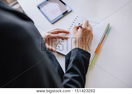 Close up shot of young businesswoman hands writing on notepad at office. Female taking notes in book.