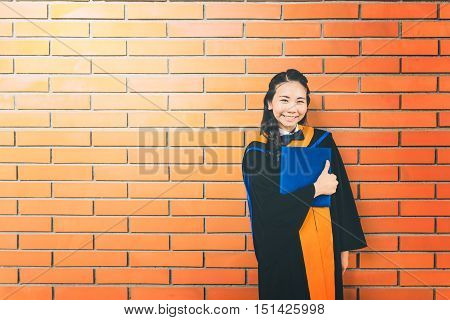 Beautiful asian university graduate student woman holding certificate thumbs up pose and smiling copy space on red brick wall background education or success concept gradient light effect