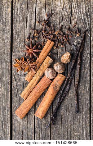 Vanilla, cinnamon, clove, nutmeg and anise star on old wooden table.