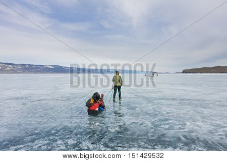 Girl With A Sledge And Trekking Pole Is On The Ice Of Lake Baikal