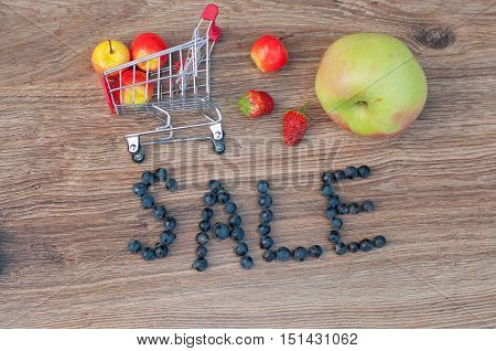 Small metal and red shopping cart and different size apples word sale made of blue grape berries laying on brown wooden table