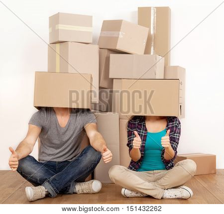 Couple with Cardboard Boxes Covering their Heads while Showing Thumbs Up