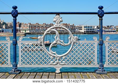 SWANAGE, UNITED KINGDOM - JULY 19, 2016 - Victorian decorative iron railings along the pier with the town to the rear Swanage Dorset England UK Western Europe, July 19, 2016.
