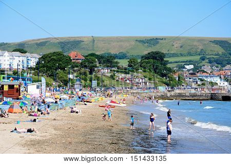 SWANAGE, UNITED KINGDOM - JULY 19, 2016 - Holidaymakers on the beach and in the sea with town buildings and harbour wall to the rear Swanage Dorset England UK Western Europe, July 19, 2016.