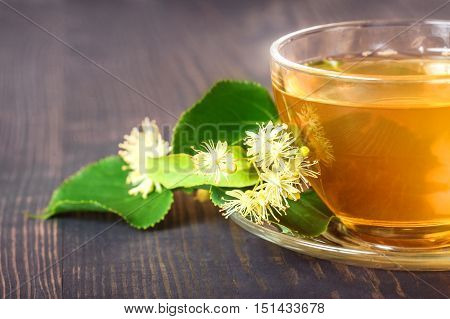 Linden tea on a wooden table in a glass cup close up. Flower tea herbal medicine.