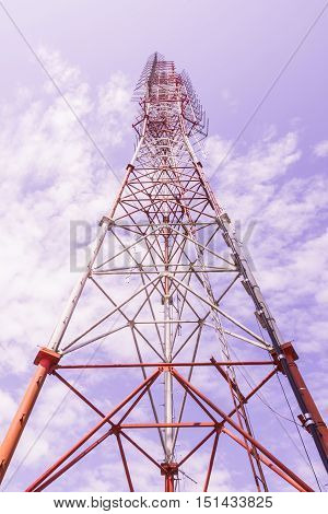 Broadcast radio tower view from bottom against blue sky and cloud background