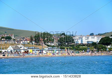 SWANAGE, UNITED KINGDOM - JULY 19, 2016 - Holidaymakers on the beach and in the sea with waterfront buildings to the rear Swanage Dorset England UK Western Europe, July 19, 2016.