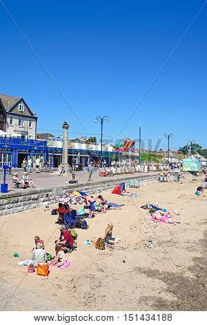 SWANAGE, UNITED KINGDOM - JULY 19, 2016 - View along the beach with holidaymakers enjoying the setting Swanage Dorset England UK Western Europe, July 19, 2016.