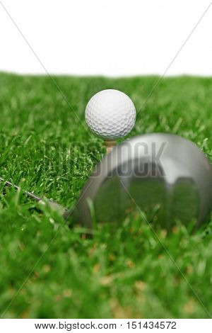 Golf Ball on Tee and Club on Golf Course