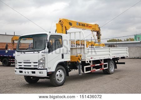 A White Isuzu flatbed truck with yellow crane arm is in the parking lot against a gray cloudy sky - Russia Moscow 30 September 2016