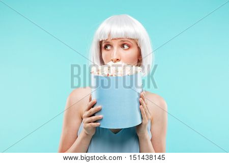 Cute playful young woman hiding her face behind the box with marshmallows