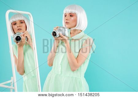 Pretty blonde young woman taking selfie using mirror and photo camera