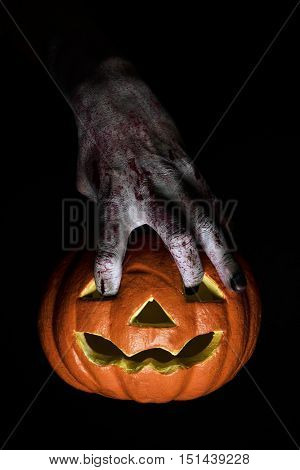closeup of the scary hand of an undead man putting his fingers in the holes of a carved pumpkin