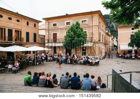 Pollensa Majorca Spain - May 24 2015. Crowded Main square Placa Major of Pollenca. People relax and enjoy communication at an outdoor.