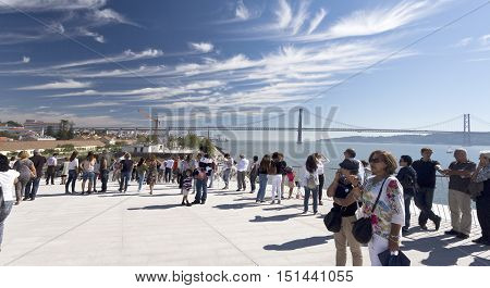 LISBON, PORTUGAL - October 5, 2016: Crowd on the roof of the MAAT (Museum of Art Architecture and Technology) with the 25th of April Suspension Bridge in the background in Lisbon Portugal