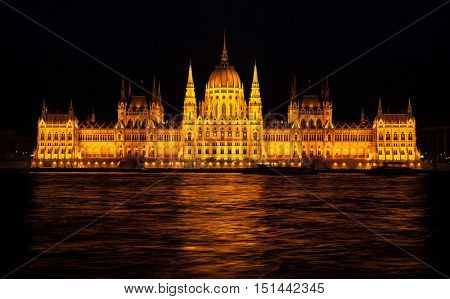 Building of Budapest parliament famous Hungarian landmark with nighttime illumination above waves Danube river in night. Hungary. Europe