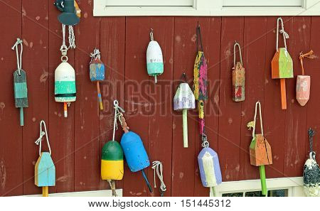 Colorful wooden buoys hanging on the side of a weathered wood building in Maine