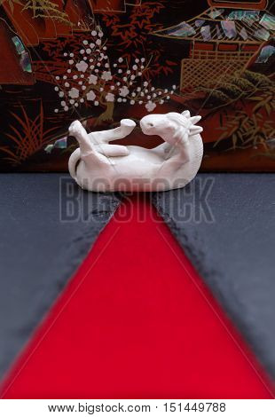 Still life of a white porcelain horse laying on its back with its feet in the air. Oriental background in red and black with leading lines. Representing luck, spirit and success.