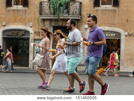 ROME ITALY - JUNE 15 2015: Tourists are going toward Spanish steps carrying the lunch. Rome Italy