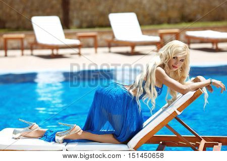 Beauty Fashion Blond Woman Model Posing In Blue Long Dress On Deck Chair, Near Blue Swimming Pool, O
