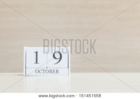Closeup surface white wooden calendar with black 19 october word on blurred brown wood desk and wood wall textured background with copy space view another more date in my portfolio
