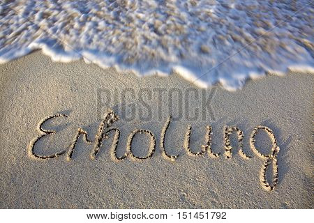 Relaxation concept. Relaxation written in sand at the beach.