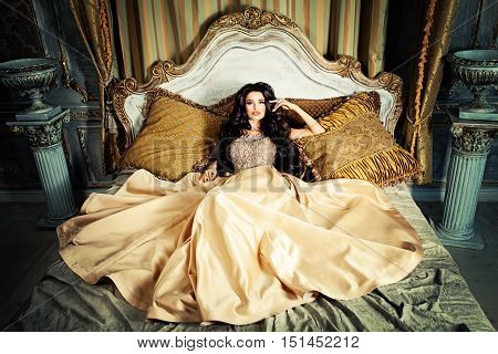 Glamorous Brunette Woman in Fashionable Dress on the bad