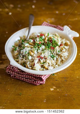 Boiled rice with white fish, toasted peanuts, chili pepper, chopped dill in a white plate, selective focus