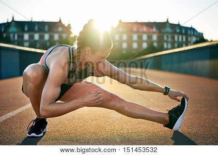 Female jogger stretches one muscular leg while placing all her weight on the other