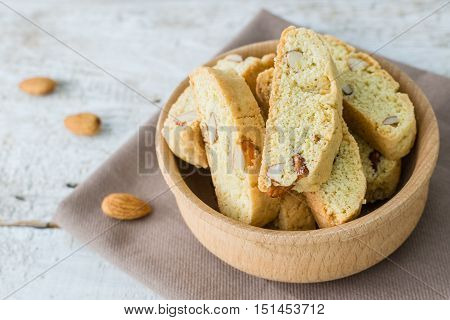 Italian cantuccini cookies in bowl with almonds. Traditional italian almond cookies biscotti on white wooden background. Homemade cookies on wooden table. Delicious cookies biscotti. Selective focus.