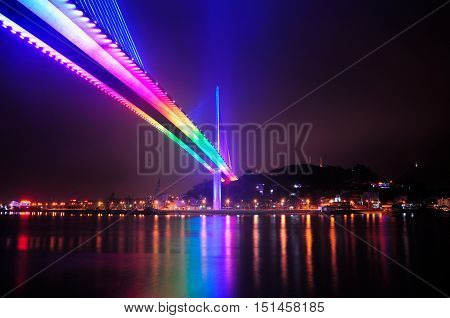 The Bai Chay Bridge in HaLong Vietnam lit up with rainbow colored lighting at night reflecting in Ha Long Bay.