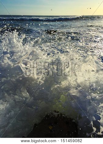 Big sea wave splash over beach rock. Huge water splash. Dangerous oceanic waves on seashore. Ocean landscape with clear blue sky horizon and foamy wave. Sunset time high tide. Seaside threat image