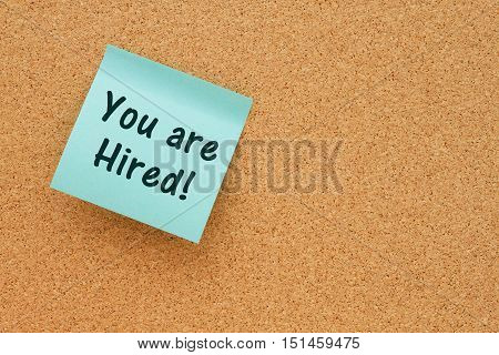 You are hired message Bulletin board with a teal sticky note with text you are hired