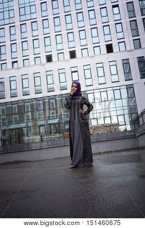 Young Muslim woman in oriental dress on a background of a modern building with a glass facade