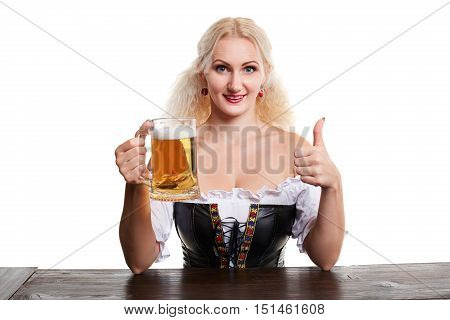 Beautiful young blond girl in traditional costume drinks out of oktoberfest beer stein. Isolated on white background. sits by the table.