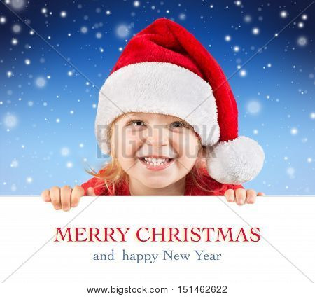 Smiling little girl looking behind a board in christmas