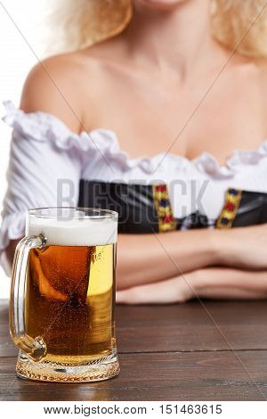 Beautiful young blond girl in traditional costume drinks out of oktoberfest beer stein. Isolated on white background. sits by the table. close-up mug