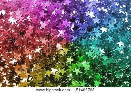 Colorful sparkling star shaped confetti closeup as a background