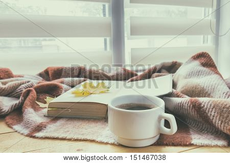 Cup of coffee and book with autumn yellow leaf surrounded wool blanket on windowsill. Coloring and processing photos in vintage style with soft selective focus.