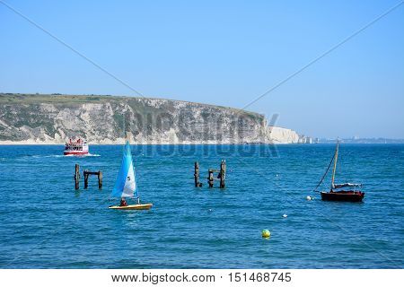 SWANAGE, UNITED KINGDOM - JULY 19, 2016 - Ferry and boats in the bay with the remains of an old wooden pier and cliffs to the rear Swanage Dorset England UK Western Europe, July 19, 2016.