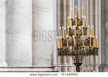 Bronze Candelabra Beside Stone Columns In A Cathedral