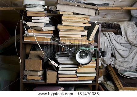 Books and other home related objects on shelves and around in mess selective focus indoor shot