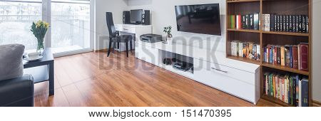 Light and spacious living room with window TV bookshelves floor panels and modern furniture panorama