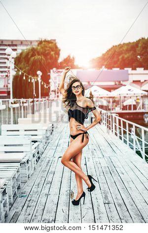 Pretty girl in black swimsuit relaxing outdoor