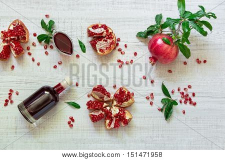 Pomegranate on a branch with leaves, broken pomegranates, seeds, leaves, gravy boat, bottle of juice on a light wooden background. Pomegranate fruits, seeds, juice and sauce. Horizontal. Top view.