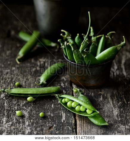 Heap of young green peas whole and broken with leaves and flower over old wooden table. Dark rustic style. Natural day light