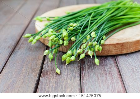 Chives flower, Garlic chives or Chinese Chive on a cutting board. Wooden background