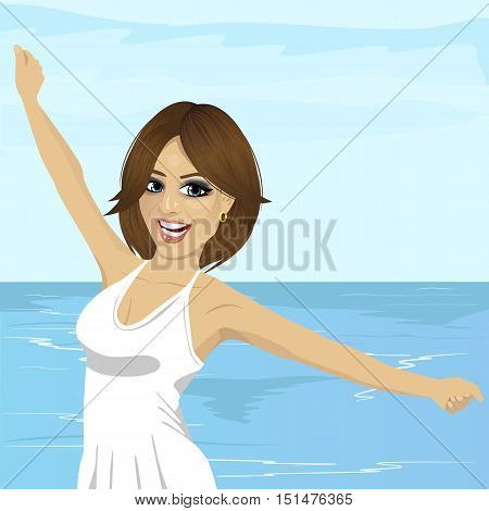 beautiful young caucasian woman with her hands raised at the beach