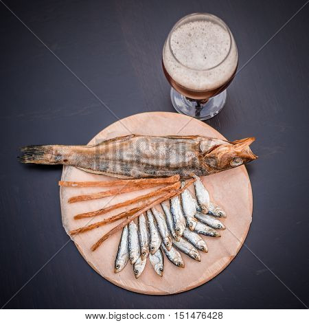 Glass of beer and assorted dried fish on a cooking sheet traditional beer snack. Black wooden background.