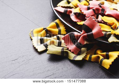 Farfalle tigrate pasta in black satine ceramics plate on dark stone background. Place for text. Concept of slow carbohydrates for healthy nutrithion.